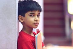Indio Little Boy con el libro de texto Imagen de archivo libre de regalías