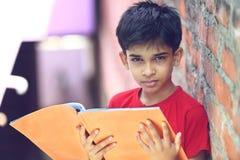Indio Little Boy con el libro de texto Fotografía de archivo libre de regalías
