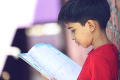 Indio Little Boy con el libro de texto Imagenes de archivo