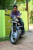 Indio masculino joven en una bici negra grande Imagenes de archivo