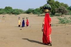 Indios con los jarros en la cabeza que se enciende para el agua bien al desierto imagenes de archivo