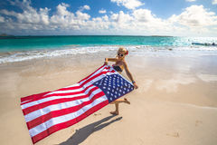 Indipendence day in Hawaii. Enjoying woman celebrate independence day waving American flag in tropical Hawaiian beach. Lanikai Beach, east shore of Oahu in royalty free stock photos