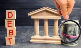 Indique a construção, os dólares e a inscrição 'débito ' Pagamento dos impostos e do débito ao estado Conceito da crise financeir fotos de stock