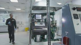 Indique de analizador líquido al empleado que va al lugar de trabajo del laboratorio almacen de metraje de vídeo