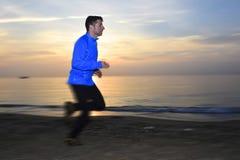 Indique la acción borrosa del hombre joven del deporte que corre al aire libre en la playa en la puesta del sol Imagen de archivo