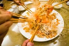 Indique las manos con los palillos que lanzan la comida de Yee Sang en Malasia Fotos de archivo