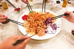 Indique las manos con los palillos que lanzan la comida de Yee Sang en Malasia Fotografía de archivo