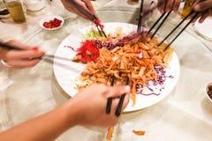 Indique las manos con los palillos que lanzan la comida de Yee Sang en Malasia Imágenes de archivo libres de regalías