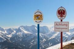 Indique los sgnboards Alemán-austríacos de la frontera en canto alpino superior de la montaña Fotos de archivo libres de regalías