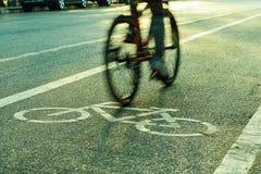 Indique a silueta borrosa a la parte del ciclista que va rápidamente en una bici Imagenes de archivo