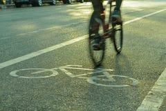 Indique a silueta borrosa a la parte del ciclista que va rápidamente en una bici Foto de archivo