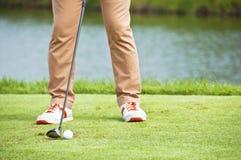 Indirizzo del colpo del T del giocatore di golf. immagini stock
