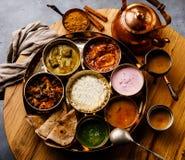 Indisch-ähnliche Mahlzeit indische Nahrung-Thali mit Hühnerfleisch und Masala-Tee Chai lizenzfreies stockfoto
