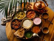 Indisch-ähnliche Mahlzeit indische Nahrung-Thali mit Hühnerfleisch und Masala-Tee Chai lizenzfreie stockfotografie