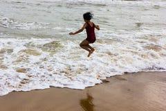 Indisch jong geitjemeisje die tegen het naderen van golf op puri zandig strand springen in kust die vreugde en opwinding uitdrukk stock fotografie