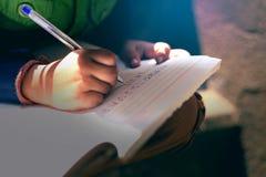 Indisch kind die op notaboek schrijven stock foto