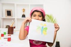 Indisch klein meisje bezig in het trekken of het schilderen of het kleuren stock foto