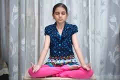 Indisch meisje die yoga doen en pranayam Stock Foto
