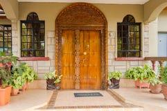 Indisch-stijl houten overwelfde galerij en ingangsdeur met twee vensters a stock afbeeldingen