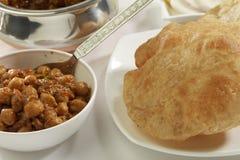Indisch Voedsel: Chana Masala en gefrituurde Puri stock foto