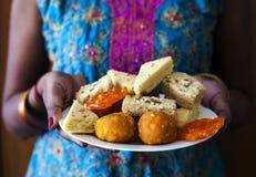 Indisch Wijfje die Indische Diwali-Snoepjes dragen stock foto