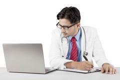 Indische arts die met laptop werken Stock Foto's