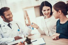 Indische arts die patiënten in bureau zien De arts geeft moeder en dochter neusnevel stock foto