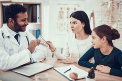 Indische arts die patiënten in bureau zien De moeder geeft geld aan arts royalty-vrije stock afbeeldingen
