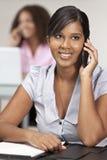 Indische asiatische Geschäftsfrau im Büro auf Handy Stockfotografie
