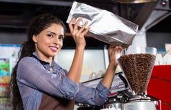 Indische barista vullende koffiemolen Stock Foto's