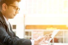 Indische bedrijfsmensen die tabletpc met behulp van bij koffie Stock Foto's