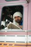Indische bestuurder in witte tulband in de cabine van zijn vrachtwagen Royalty-vrije Stock Foto's