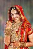 Indische Braut in ihrer Hochzeitskleidvertretung Stockfotos