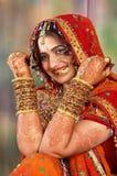 Indische bruid in haar huwelijkskleding die armbanden toont Stock Afbeeldingen