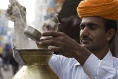 Indische Chai-Arbeitskraft, die etwas Tee gießt Stockbilder