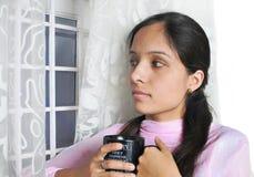 Indische dame die van koffie geniet. Stock Foto
