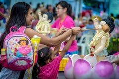 Indische Dame mit der Tochter, die den Buddha während Vesak-Tages badet lizenzfreie stockfotos
