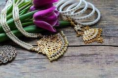 Indische decoratie voor het dansen: armbanden, halsband Purpere ultraviolette tulpen op oude rustieke houten achtergrond royalty-vrije stock afbeelding