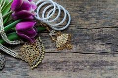Indische decoratie voor het dansen: armbanden, halsband Purpere ultraviolette tulpen op oude rustieke houten achtergrond stock foto