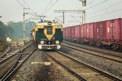 Indische Eisenbahnen drängten Nahverkehrszug, eine Station auf einem nebeligen Wintermorgen ungefähr einzutragen Lizenzfreie Stockbilder