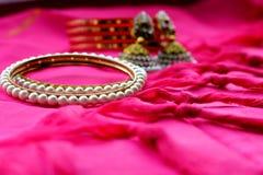 Indische ethnische Schmuckarmbänder und -ohrringe auf rosa Gewebe lizenzfreie stockfotos