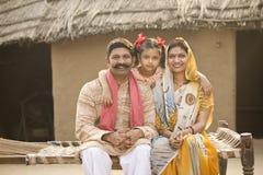 Indische Familie, die auf traditionellem Bett im Dorf sitzt lizenzfreie stockfotografie