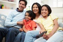 Indische Familie, die zusammen im Sofa Watching Fernsehen sitzt Lizenzfreie Stockfotos