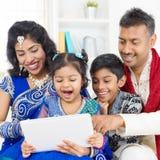 Indische Familie unter Verwendung der Digitalrechnertablette Stockfotos