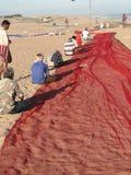 Indische Fischer, die ihre Netze reparieren Stockfoto