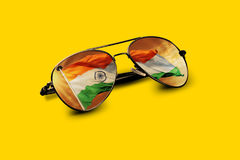 Indische Flagge dachte über Flieger Sunglasses auf Gelb nach Stockfotografie