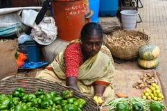 Indische Frau, die Erzeugnis am Markt verkauft stockfotografie
