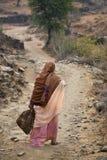 Indische Frau, die hinunter Landweg geht stockbild
