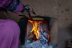 Indische Frau, die Roti in traditionellem Ofen chulha unter starken Bedingungen macht stockbild
