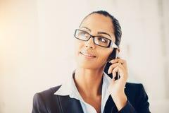 Indische Geschäftsfrau, die den Handy glücklich verwendet Stockfoto